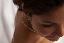Karine est coiffée avec des épingles bijoux constellation blanche en nacre . Elle porte un collier fin en navre et des boucles d'oreilles courtes en nacre et argent.